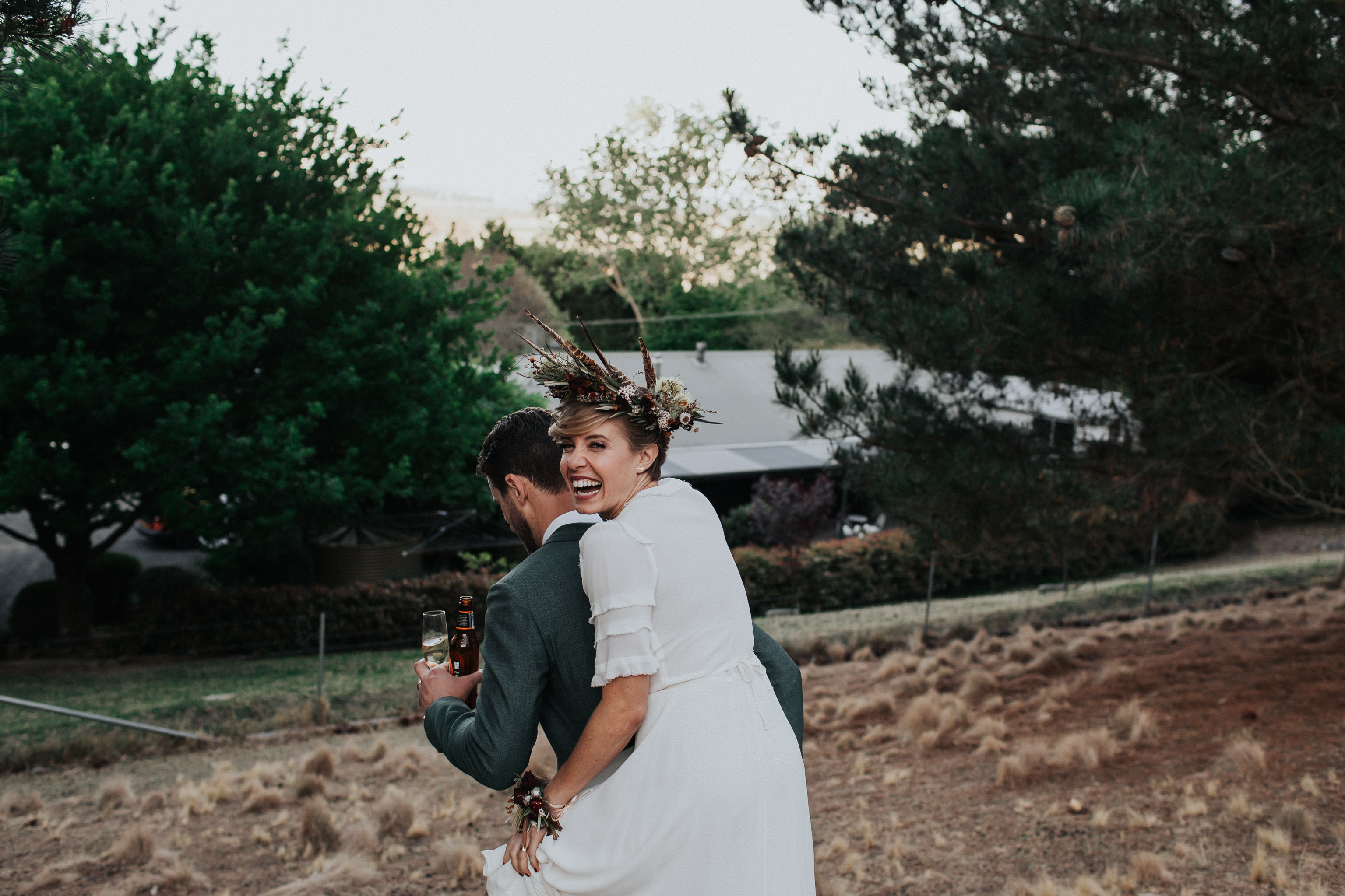 Bride piggy backing on groom laughing