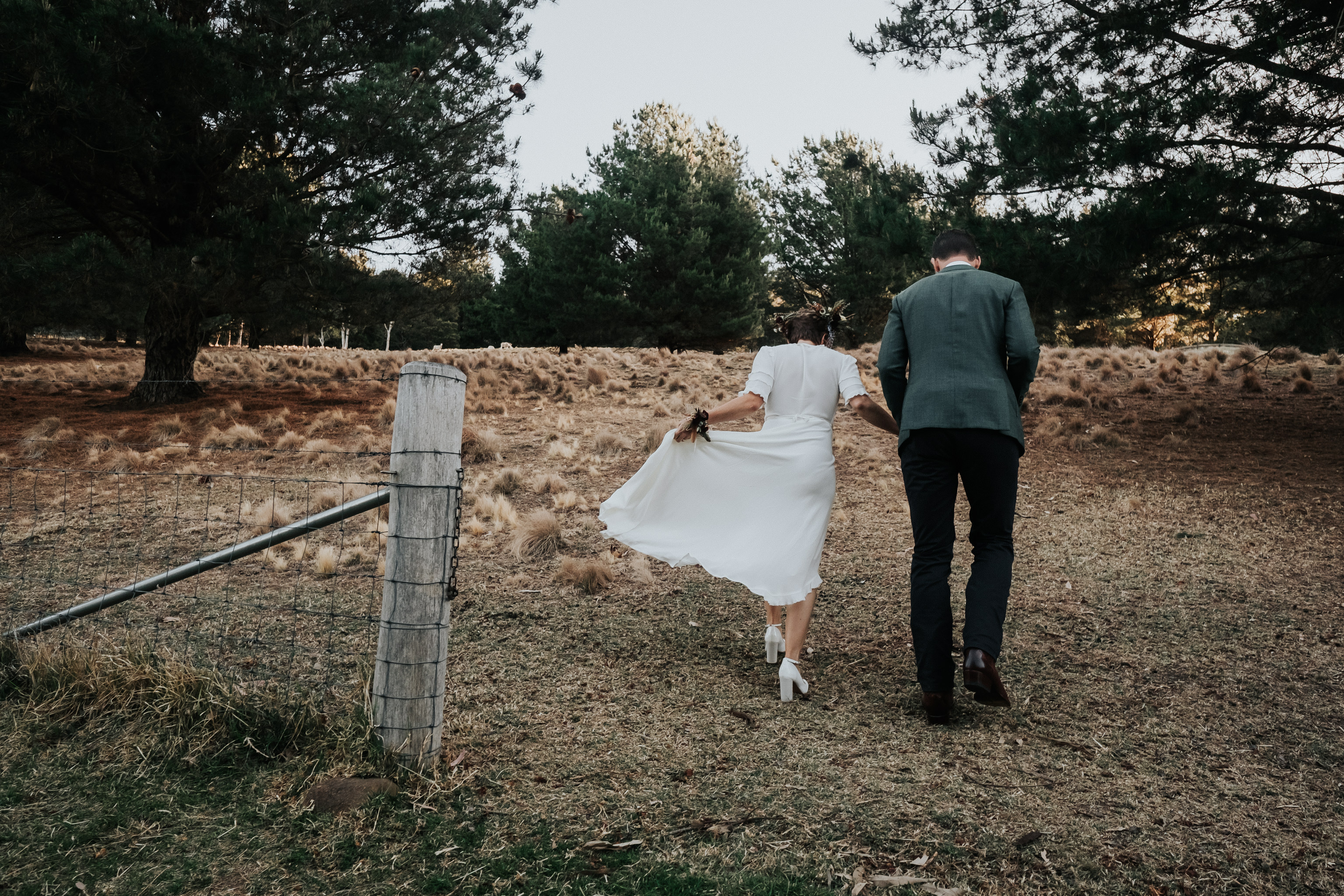 Bride and groom walking up hill holding skirt