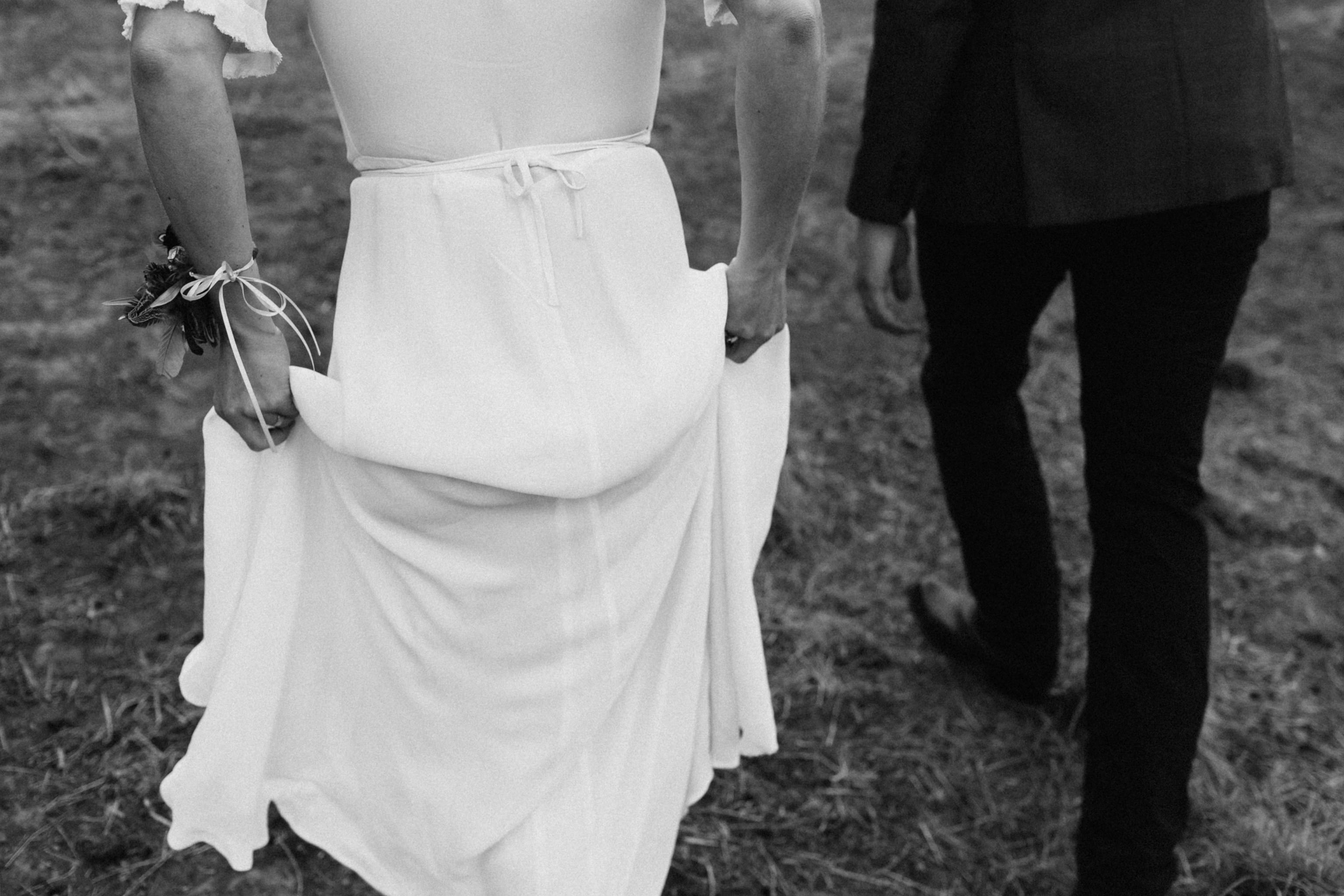 Black and white closeup of bride holding skirt