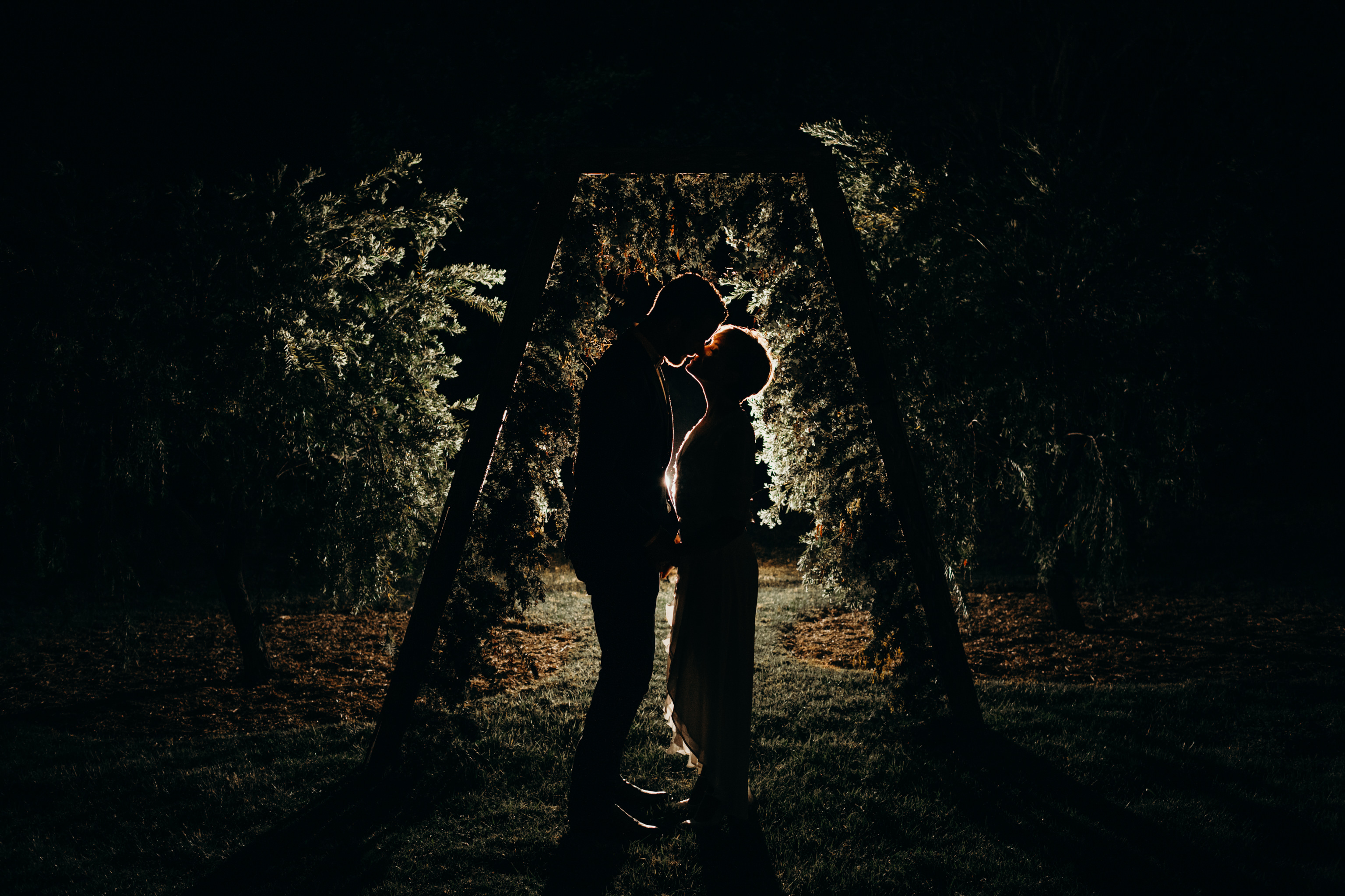 Bride and groom back lit under arbour kissing